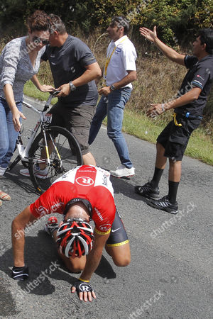 A woman comes tries to help Janez Brajkovic of Slovenia after he crashed in the fifth stage of the Tour de France cycling race over 164.5 kilometers (102.2 miles) starting in Carhaix and finishing in Cap Frehel, Brittany, western France, . Brajkovic was unable to continue the race