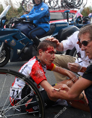 A Tour de France medic and a team member tend to Janez Brajkovic of Slovenia who crashed and subsequently abondoned the race during the fifth stage of the Tour de France cycling race over 164.5 kilometers (102.2 miles) starting in Carhaix and finishing in Cap Frehel, Brittany, western France