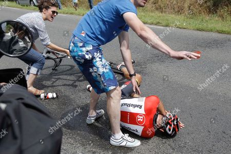Spectators come to the aid of Janez Brajkovic of Slovenia after he crashed in the fifth stage of the Tour de France cycling race over 164.5 kilometers (102.2 miles) starting in Carhaix and finishing in Cap Frehel, Brittany, western France, . Brajkovic was unable to continue the race