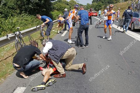 A Tour de France doctor tends to Janez Brajkovic of Slovenia as Robert Gesink of The Netherlands, rear, is helped back on his bicycle, after several riders crashed in the fifth stage of the Tour de France cycling race over 164.5 kilometers (102.2 miles) starting in Carhaix and finishing in Cap Frehel, Brittany, western France, . Brajkovic abandoned the race