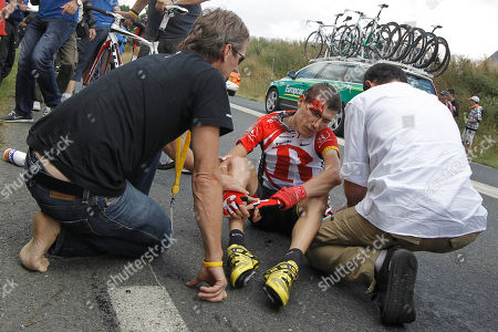 A Tour de France doctor, right, treats Janez Brajkovic of Slovenia who crashed and subsequently abondoned the race during the fifth stage of the Tour de France cycling race over 164.5 kilometers (102.2 miles) starting in Carhaix and finishing in Cap Frehel, Brittany, western France