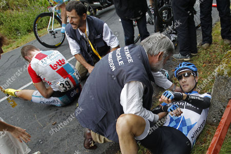 Tour de France doctors tend to David Zabriskie of the US, right, and Frederik Willems of Belgium, left, after they crashed during the 9th stage of the Tour de France cycling race over 208 kilometers (129 miles) starting in Issoire and finishing in Saint Flour, central France