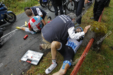 Tour de France doctors tend to David Zabriskie of the US, right, and Frederik Willems of Belgium, left, aftre they crashed during the 9th stage of the Tour de France cycling race over 208 kilometers (129 miles) starting in Issoire and finishing in Saint Flour, central France