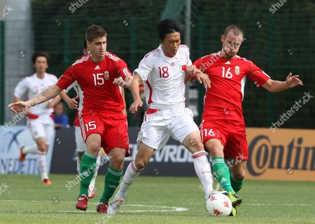 Stock Image of Xie Pengfei, Adam Simon, Mate Kiss China's forward Xie Pengfei, center, challenges for the ball with Hungary's midfielder Adam Simon, right, and midfielder Mate Kiss, during their match in the Under-21 Toulon soccer Tournament, in Hyeres, southern France