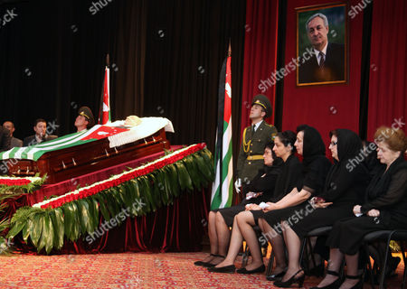 Relatives of Sergei bagaph, right, sit near a coffin of Abkhazia's separatist President Sergei Bagapsh during a farewell ceremony in Sukhumi, on . Bagapsh died in a hospital on Sunday, May 29, aging 62