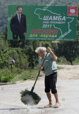 A man sweeps the road near a poster of one of three presidential candidates Sergei Shamba's in Sukhumi capital of Georgian breakaway region of Abkhazia, . The elections was announced for Friday, Aug. 26 following the death of President Sergei Bagapsh in May. All the three hopefuls are seasoned pro-Kremlin politicians opposed to reunification with the central Georgian government
