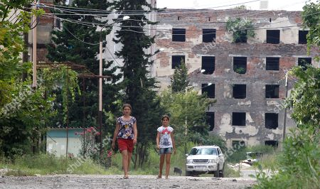 Abkhazian girls walk along a street of war-damage apartment buildings in Sukhumi, the capital of the Georgian breakaway region of Abkhazia, . Presidential elections were announced in Abkhazia for Friday, August 26 following the death of President Sergei Bagapsh in May