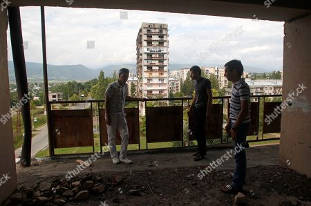 Abkhazians stand on the balcony of war-damage apartment building in Sukhumi, the capital of the Georgian breakaway region of Abkhazia, . Presidential elections in Abkhazia were announced for Friday, August 26 following the death of President Sergei Bagapsh in May
