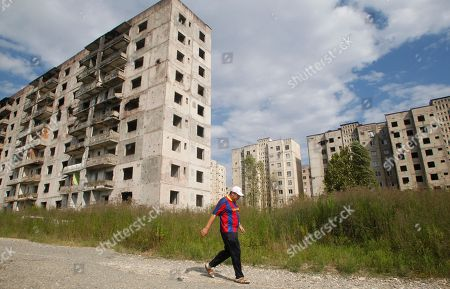 Stock Image of An Abkhazian man walks past war-damaged apartment buildings in Sukhumi, the capital of the Georgian breakaway region of Abkhazia, . Presidential elections in Abkhazia were announced for Friday, August 26 following the death of President Sergei Bagapsh in May