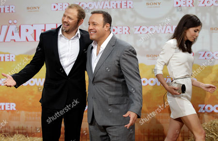 US actor Kevin James, center, and German comedian and voice actor Mario Barth who speaks the monkey Donald, left, pose for the photographers during the Europe premiere of the movie 'The Zookeeper' in Berlin, Germany, . At right is German actress and voice actor of the Giraffe Mollie, Nadine Warmuth