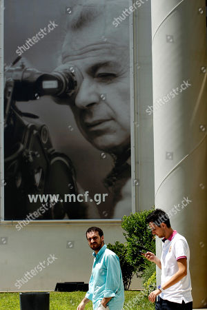 """Two men walk out of the Michael Cacoyannis Foundation in Athens under a poster-size photo of the Cyprus-born filmmaker Michael Cacoyannis, on . Cacoyannis whose directing credits included the 1964 movie """"Zorba the Greek,"""" starring Anthony Quinn, has died at an Athens hospital on Monday, July 25, 2011. He was 89"""