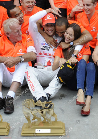 Lewis Hamilton, Jenson Button, Jessica Michibata, John Button McMcLaren Mercedes driver Lewis Hamilton of Britain, centre right, hugs Jenson Button of Britain and Button's girlfriend Jessica Michibata as his father John Button looks on after Button's victory at the Hungarian Grand Prix in Hungaroring circuit outside Budapest
