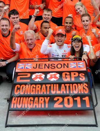 Jenson Button, Jessica Michibata, John Button McLaren Mercedes driver Jenson Button, of Britain front centre, sits with his girlfriend Jessica Michibata right, and his father John Button as they react for the cameras after Button's victory at the Hungarian Grand Prix in Hungaroring circuit outside Budapest