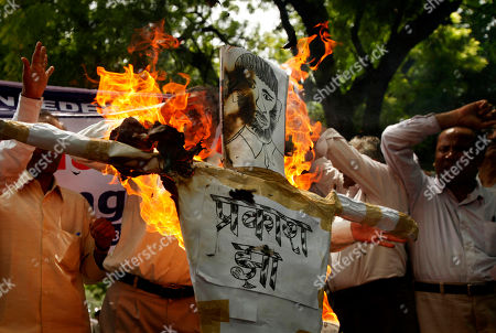 "Activists of All India Federation of Scheduled Caste/Scheduled Tribes Organizations burn an effigy of Bollywood director Prakash Jha at a protest against his latest film ""Aarakshan,"" or ""Reservation"" in New Delhi, India, . Protestors say the film speaks against India's affirmative action program that reserves education seats and jobs for the country's indigenous peoples and its dalits, or untouchables, who have no caste and have suffered centuries of severe discrimination, and members of other lower castes. 3 Indian states have banned the movie following apprehensions that certain scenes and dialogues may trigger trouble, according to a news agency"