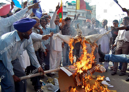 "Bahujan Samaj Party activists burn an effigy of Bollywood Director Prakash Jha as they protest against the release of his latest film ""Aarakshan,"" or ""Reservation,"" during a protest against the film in Amritsar, in the northern Indian state of Punjab, . The protestors say the film speaks against India's affirmative action program that reserves education seats and jobs for the country's indigenous peoples and its dalits, or untouchables, who have no caste and have suffered centuries of severe discrimination, and members of other lower castes. Punjab is among 3 states that have banned the movie, slated to be released Friday, following apprehensions that certain scenes and dialogues may trigger trouble, according to a news agency"