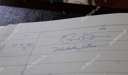 U.S. President Barack Obama and first lady Michelle Obama's signatures are seen in the guest book as they visit with Ireland's President Mary McAleese and husband Martin McAleese at the presidential residence in Dublin, Ireland