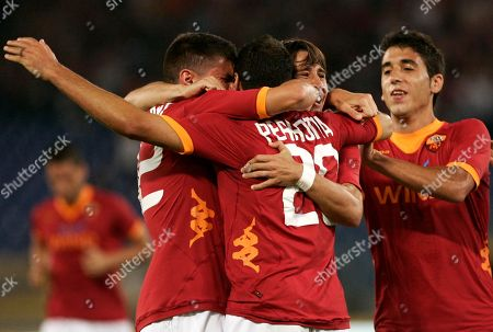 AS Roma midfielder Simone Perrotta, center back to camera, is hugged by teammates Federico Viviani, left, and Bojan Kirkic, of Spain, second from right, after scoring during a UEFA Europa League playoff second leg soccer match against Slovan Bratislava, at Rome's Olympic stadium