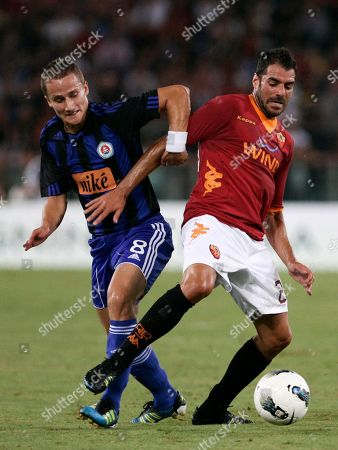 Erik Grendel, Simone Perrotta AS Roma midfielder Simone Perrotta, right, is challenged by Slovan Bratislava midfielder Erik Grendel during a UEFA Europa League playoff second leg soccer match at Rome's Olympic stadium