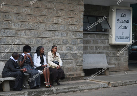 Triza Njeri, wife of the late Kenyan runner Sammy Wanjiru, second left, wait with relatives at a funeral home in Nairobi, Kenya, before going to Nyaharuru, where Wanjiru will be buried. Wanjiru, who set a blistering pace to shatter the 24-year-old Olympic record in the marathon, died on May 15 in Nyahururu, Kenya