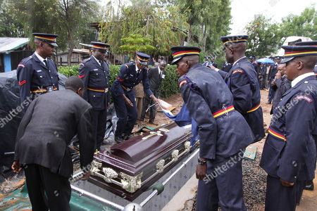 Kenyan police officers carry the coffin containing the body of the late Kenyan runner Sammy Wanjiru at in Nyahururu, on . Olympic marathon champion Samuel Wanjiru was interred today after weeks of a tussle over his burial between his wife and his mother who insists the athlete was killed