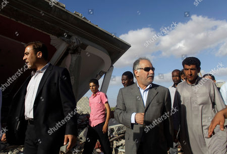 On a government-organized tour Libyan Prime Minister Al-Baghdadi Ali Al Mahmoudi, second from right, and Libyan government spokesman Moussa Ibrahim, left, inspect the damage along with an entourage of nations' ambassadors that were brought along, at a home that was destroyed during a NATO airstrike a day earlier in the town of Majar, near Zlitan, Libya, . According to the Libyan government, 85 civilians were killed during the airstrikes