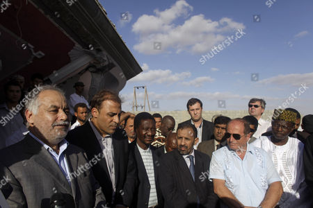 On a government-organized tour Libyan Prime Minister Al-Baghdadi Ali Al Mahmoudi, left, and Libyan government spokesman Moussa Ibrahim, second from left, speak to an entourage of nations' ambassadors that were brought along at a home that was destroyed during a NATO airstrike a day earlier in the town of Majar, near Zlitan, Libya, . According to the Libyan government, 85 civilians were killed during the airstrikes