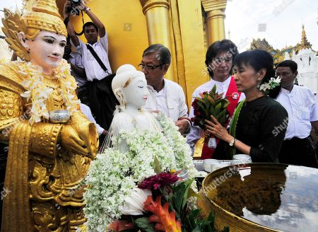 Aung San Suu Kyi, Kim Aris Myanmar democracy icon Aung San Suu Kyi, 2nd right, offers flowers to a Buddha statue during her visit to the Shwedagon pagoda in Yangon, Myanmar, with her youngest son Kim Aris, 3rd right, and members of National League for Democracy party