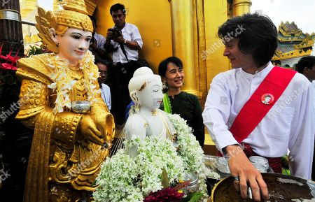 Aung San Suu Kyi On, Myanmar opposition leader Aung San Suu Kyi, center, smiles at her youngest son, Kim Aris as Kim pours water to Buddha image during their visit to Myanmar Land mark Shwedagon pagoda in Yangon, Myanmar