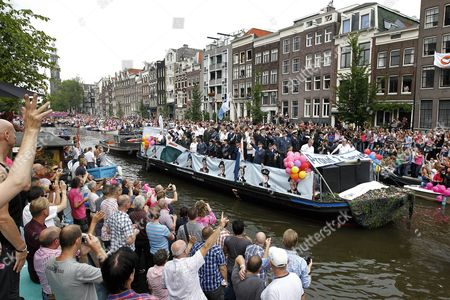 """Embracing a policy of """"Do Tell"""" the Dutch military joins Amsterdam's annual Gay Pride parade for the first time this year in Amsterdam, The Netherlands, . Uniformed men and women saluting the crowds from a boat chugging through the city's canals. Invited guests on the boat are former US Army Lt. Dan Choi, discharged after he violated the """"Don't ask don't tell"""" policy, and British naval Lt. Cdr. Mandy McBain"""