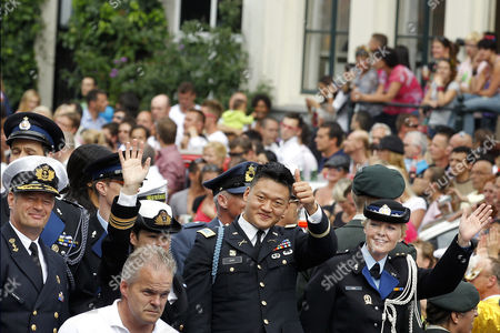 """Lt. Dan Choi, second right, a discharged openly gay U.S. Army veteran who has been an outspoken critic of the military's """"don't ask, don't tell"""" policy takes part in the Gay Pride canal parade in Amsterdam, The Netherlands, . The Dutch Defense Ministry is sponsoring a boat in the annual festival for the first time this year, underscoring the long-standing policy of accepting of homosexuals in the military, starkly contrasting with the """"Don't Ask, Don't Tell"""" (DADT) policy of the US military"""