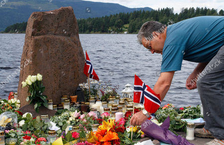A man places a Norwegian flag between flowers in Utvika in front of the Utoya island, near Oslo, Norway, where a gunman Anders Behring Breivik killed at least 76 people. The defense lawyer for Anders Behring Breivik said Tuesday his client's case suggests he is insane, adding that someone has to take the job of defending him but that he will not take instructions from his client. Geir Lippestad told reporters that the suspect in the bombing on the capital and the brutal attack on a youth camp that killed at least 76 people is not aware of the death toll or of the public's response to the massacre that has rocked the country