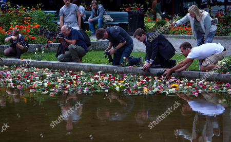 Photographers take photos of flowers thrown by people into a fountain in memory of the victims of Friday's bomb attack and shooting rampage in Oslo, Norway, . The defense lawyer for Anders Behring Breivik said Tuesday his client's case suggests he is insane, adding that someone has to take the job of defending him but that he will not take instructions from his client. Geir Lippestad told reporters that the suspect in the bombing on the capital and the brutal attack on a youth camp that killed at least 76 people is not aware of the death toll or of the public's response to the massacre that has rocked the country