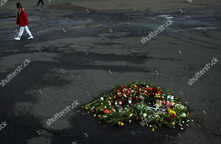 People walk past flowers in memory of the victims of Friday's bomb attack and shooting rampage in Oslo, Norway, . The defense lawyer for Anders Behring Breivik said Tuesday his client's case suggests he is insane, adding that someone has to take the job of defending him but that he will not take instructions from his client. Geir Lippestad told reporters that the suspect in the bombing on the capital and the brutal attack on a youth camp that killed at least 76 people is not aware of the death toll or of the public's response to the massacre that has rocked the country