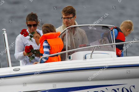 A family drops red roses from their boat into the sea close to Utoya island, near Oslo, Norway, where gunman Anders Behring Breivik killed at least 76 people. The defense lawyer for Anders Behring Breivik said Tuesday his client's case suggests he is insane, adding that someone has to take the job of defending him but that he will not take instructions from his client. Geir Lippestad told reporters that the suspect in the bombing on the capital and the brutal attack on a youth camp that killed at least 76 people is not aware of the death toll or of the public's response to the massacre that has rocked the country