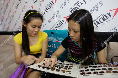 Kins Wu, right, a Filipino hotel worker sifts through hair color samples similar to her singer idol Sandara Park inside the Manila branch of a Korean salon, Philippines. Just as it has elsewhere in Asia, South Korean popular culture, from music and TV dramas to fashion and cosmetics, is captivating many in the Philippines, once an undisputed bastion of American pop and Hollywood movies