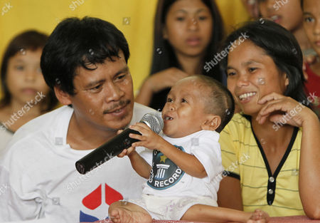 "Junrey Balawing, Reynaldo Balawing, Concepcion Balawing Reynaldo, left, and Concepcion Balawing, parents of Junrey Balawing, center, react as Junrey jokes on a microphone after he was officially declared ""the world's shortest living man"" by the Guinness World Records at Sindangan Municipal Hall in Sindangan township, Zamboanga Del Norte province in Southern Philippines, on his 18th birthday and coincidentally the Philippines' Independence Day. Balawing was officially declared ""the world's shortest living man"" with a measurement of 23.5 inches (59.93 centimeters) dislodging Nepal's Khagendra Thapa Magar with a measurement of 26.4 inches (67 centimeters"