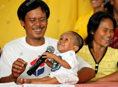 Junrey Balawing Reynaldo, left, and Concepcion Balawing, parents of Junrey Balawing, center, 18, react as Junrey jokes on the microphone after he was officially declared 'the world's shortest living man' by the Guinness World Records at Sindangan Municipal Hall, Sindangan township, Zamboanga Del Norte province in Southern Philippines, . Balawing was officially declared 'the world's shortest living man' with a measurement of 59.93 Centimeters (23.5 inches) dislodging Nepal's Khagendra Thapa Magar with a measurement of 26.4 inches