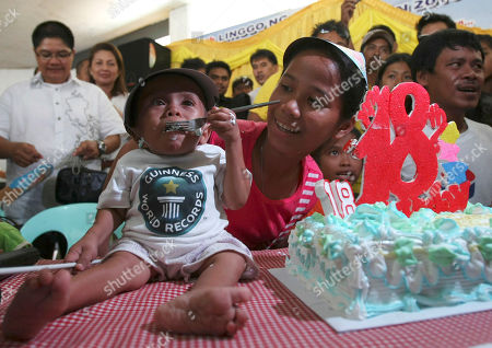 "Junrey Balawing Junrey Balawing eats his cake after he was officially declared ""the world's shortest living man"" by the Guinness World Records at Sindangan Municipal Hall, Sindangan township, Zamboanga Del Norte province in Southern Philippines, his 18th birthday and coincidentally the Philippines' Independence Day. Balawing was officially declared ""the world's shortest living man"" with a measurement of 23.5 inches (59.93 centimeters) dislodging Nepal's Khagendra Thapa Magar with a measurement of 26.4 inches"