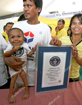 Stock Picture of Junrey Balawing, Reynaldo Balawing, Concepcion Balawing Junrey Balawing smiles as he poses with his Guinness World Records certificate declaring him the world's shortest living man following the last of a series of measurements conducted at Sindangan Municipal Hall, Sindangan township, Zamboanga Del Norte province in Southern Philippines, his 18th birthday and coincidentally the Philippines' Independence Day. Balawing was officially measured at at 23.5 inches (59.93 centimeters) dislodging Nepal's Khagendra Thapa Magar with a measurement of 26.4 inches. Holding him is his father Reynaldo and his mother Concepcion at right