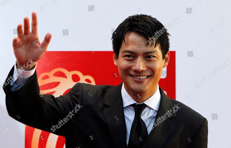 """Archie Kao American actor Archie Kao waves to photographers during the red carpet movie premier of the movie """"Larry Crowne"""" in Singapore"""