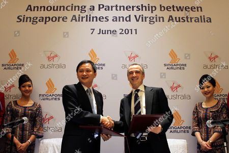 John Borghetti, Goh Choon Phong Virgin Australia group of airlines CEO John Borghetti, center right, and Singapore Airlines CEO Goh Choon Phong shake hands after signing an agreement between the two airline companies on in Singapore on the sidelines of The Air Transport Association (IATA) 67th Annual General Meeting and World Air Transport Summit
