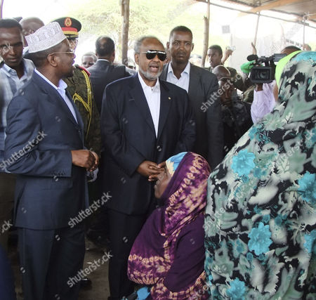 Djibouti president Ismael Omar Guelleh, middle,in dark glasses and Somali president Sheik Sharif Ahmed, left, speak to a woman and her child at Badbado refugee camp in Somalia's capital Mogadishu, . Omar Guelleh is on a visit in the Somali capital to see the scale of the famine in Somalia