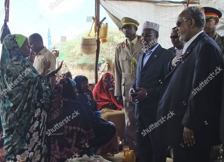 Djibouti president Ismail Omar Guelleh, right, and Somalia's President Sheik Sharif Ahmed, second right, talk to refugees as they visit a refugee camp in Mogadishu Somalia