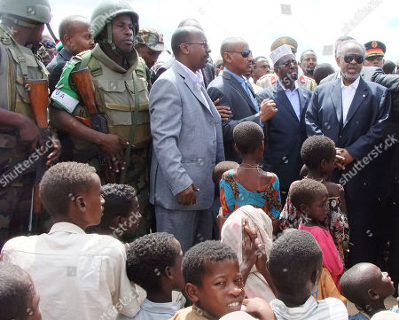 Djibouti president Ismail Omar Guelleh, right, and Somalia's President Sheik Sharif Ahmed, second right, talks to refugees as they visit a refugee camp in Mogadishu Somalia