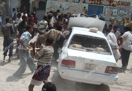 Somali protesters smash a car believed to belong to a Somali Member of Parliament, in Mogadishu, Somalia, where demonstrators took to the streets for the second day in support of current Prime Minister Mohamed Abdullahi Farmajo. A new accord extending the government's term by a year requires Prime Minister Mohamed Abdullahi Mohamed to resign in a month, but Mohamed is popular with many Somalis because he has managed to pay salaries for government workers and soldiers and attack corruption since he came to power in October last year