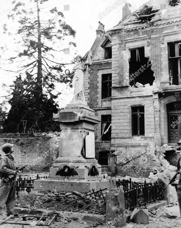 Stock Photo of Pvt. Roy Jenkins, of San Antonio, Tex., a cousin of Lew Jenkins, the boxer, examines the ruins and devastation of a street in Periers, France in an undated photo, after the town was taken by the American forces