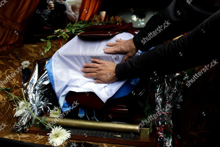 Mourners place their hands on the flag-draped coffin containing the remains of Argentine author Ernesto Sabato in Buenos Aires, Argentina, . Sabato, who led the government's probe of crimes committed by Argentina's dictatorship, died early Saturday in his home. He was 99