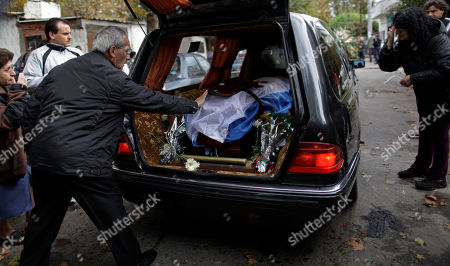 A mourner reaches out to touch the flag-draped coffin containing the remains Argentine author Ernesto Sabato in Buenos Aires, Argentina, . Sabato, who led the government's probe of crimes committed by Argentina's dictatorship, died early Saturday in his home. He was 99
