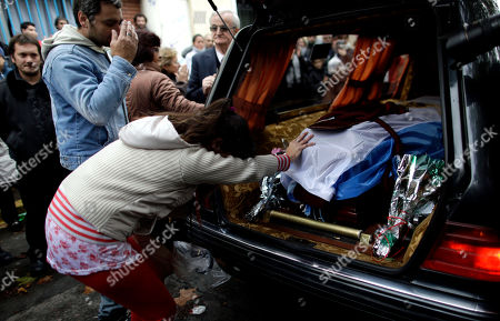 A mourner touches the flag-draped coffin containing the remains of Argentine author Ernesto Sabato in Buenos Aires, Argentina, . Sabato, who led the government's probe of crimes committed by Argentina's dictatorship, died early Saturday in his home. He was 99