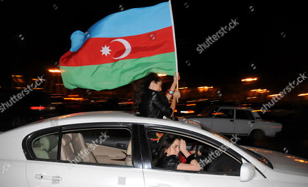 Stock Photo of Azerbaijani girls wave a national flag in Baku, Azerbaijan, as they celebrate victory in the final of the Eurovision Song Contest 2011 by Nigar Jamal and Eldar Gasimov from Azerbaijan with their song 'Running Scared'. More than 120 million viewers around the globe tune in to watch the spectacle that has taken place every year since 1951. Organizers said the production this year in Germany's Fortuna Duesseldorf Arena cost euro12 million ($17 million